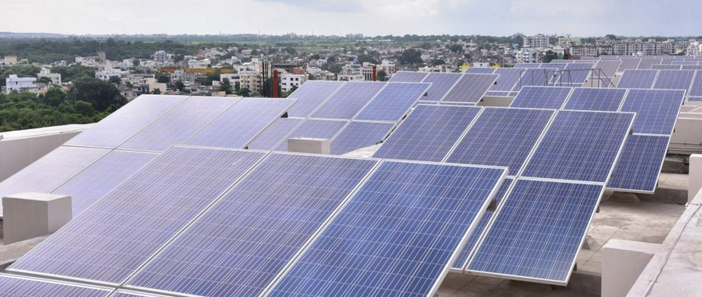 An array of solar panels with a city scape and horizon in the background.